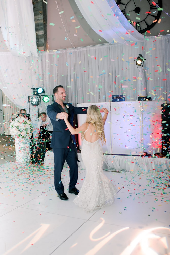 Bride and groom dancing with each other while confetti is blowing at Larkspur events and dining wedding reception