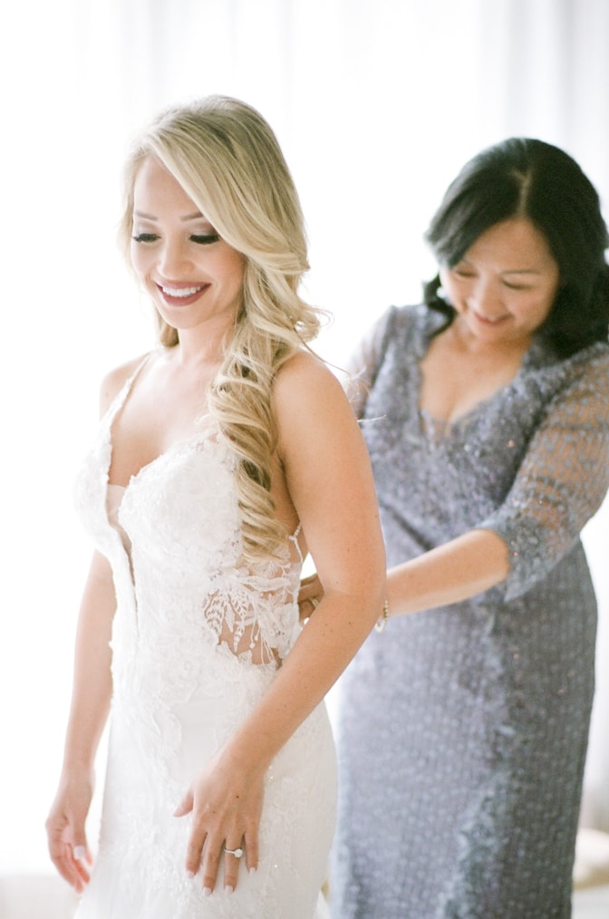 Bride getting into her dress with the help of her mom in the wedding suite of Four Seasons Vail
