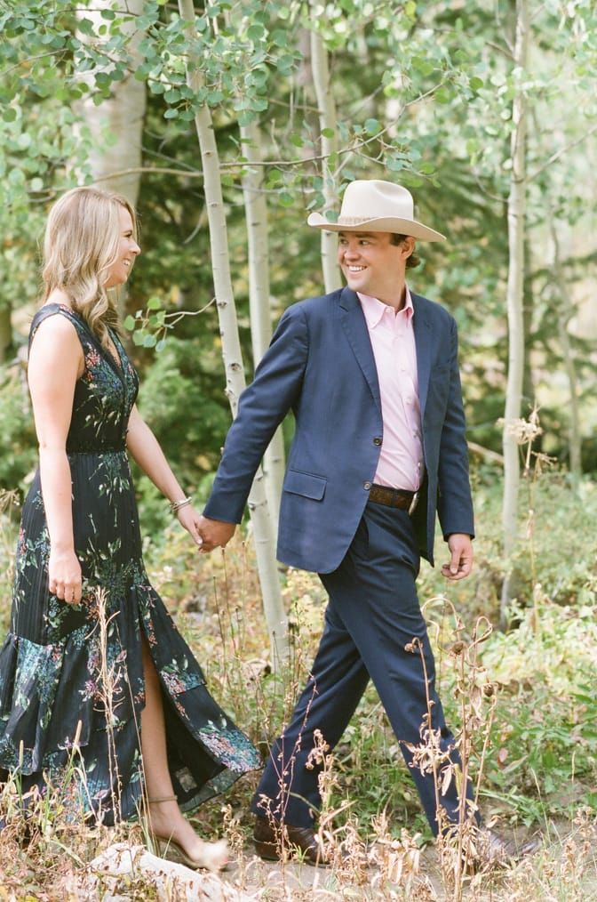 Bride and groom holding hands and walking in between Aspens in Aspen