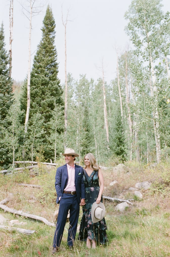Bride and groom holding hands and standing in a forest in Aspen