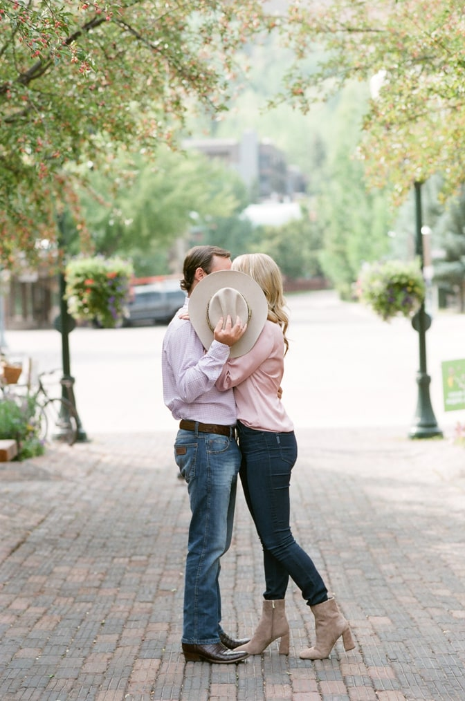 Bride and groom kissing behind a cowboy hat in Aspen town