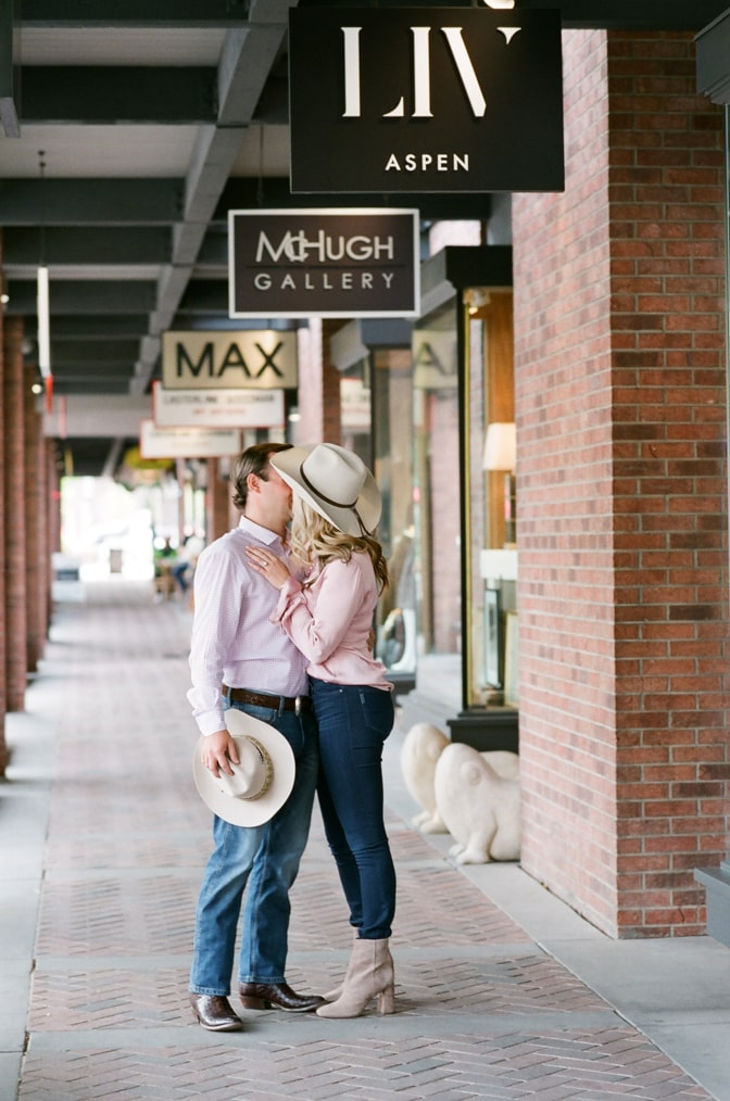 Bride and groom kissing each other in shop alley in Aspen town