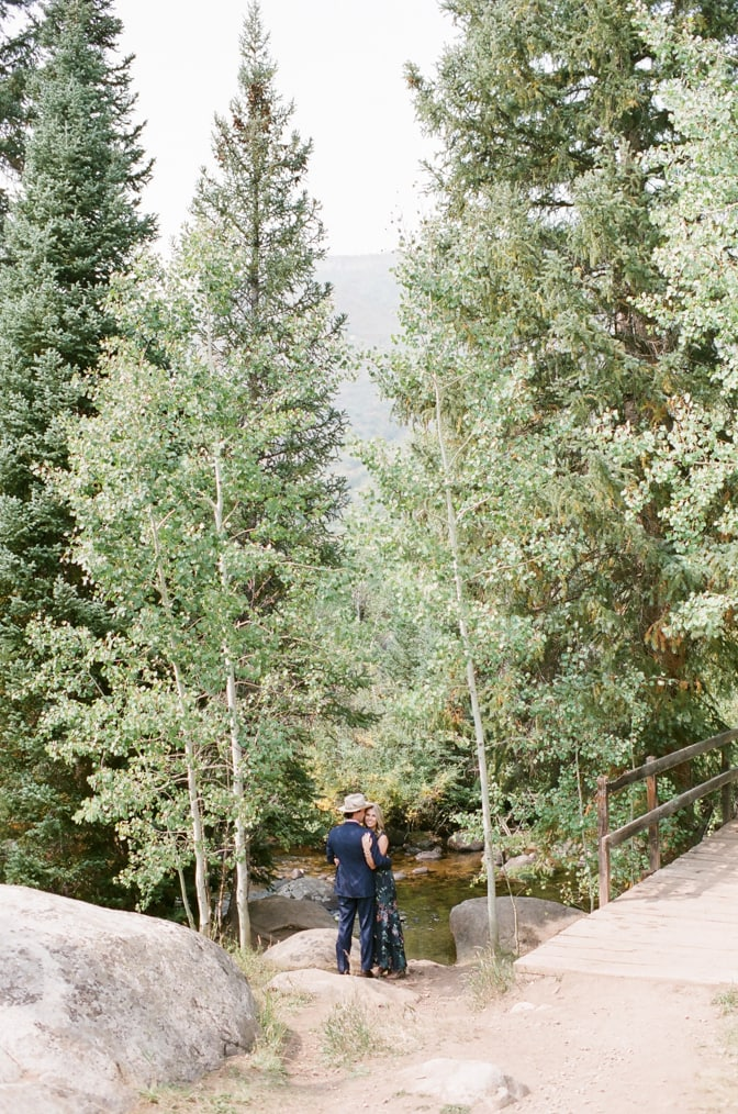 Bride and groom embracing each other near a creek in Aspen