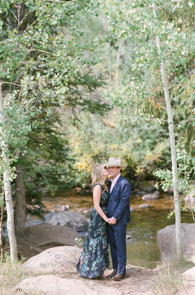 Bride and groom talking to each other near a creek in Aspen