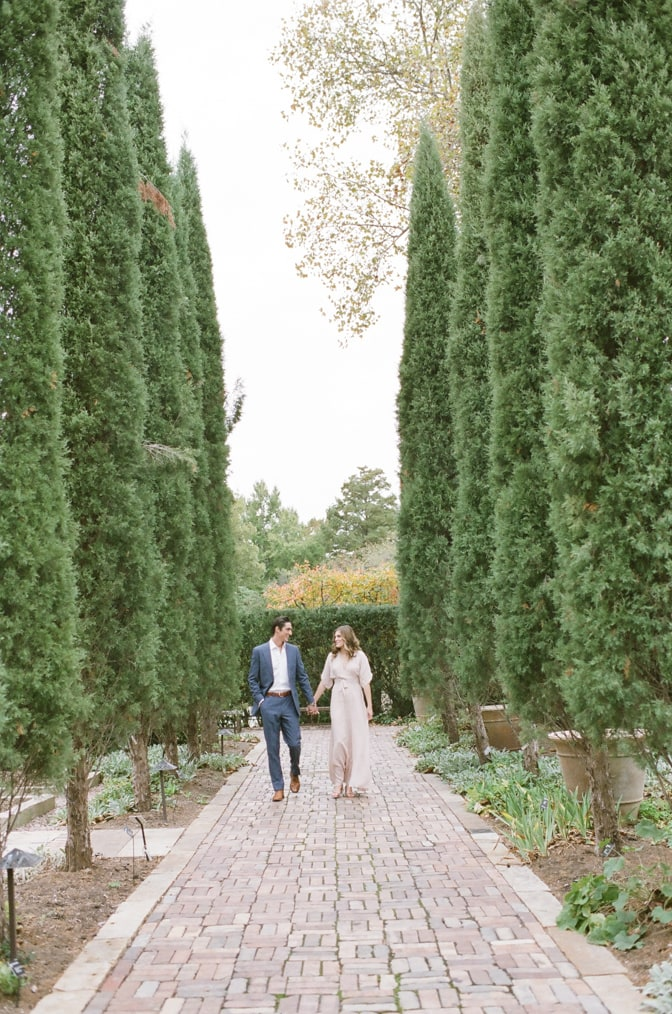 Bride and groom walking hand in hand amongst majestic cypresses in St Louis