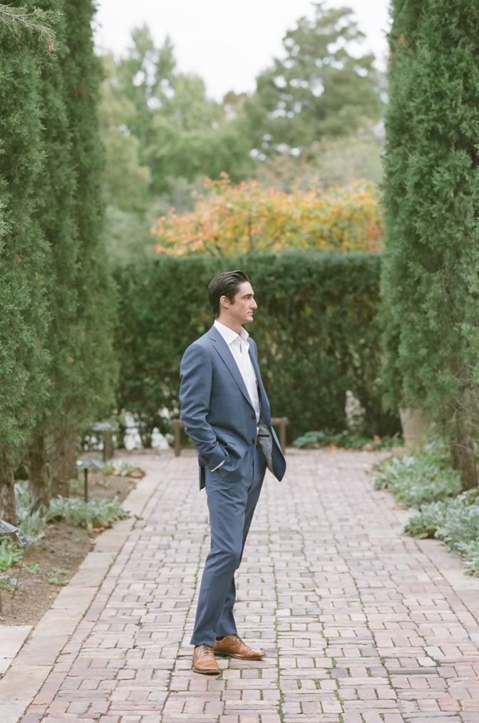 Groom facing a row of cypresses during his St Louis engagement