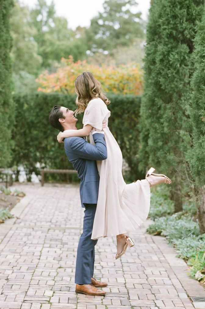 Groom lifting his bride in an alley of majestic cypresses at Missouri Botanic Garden