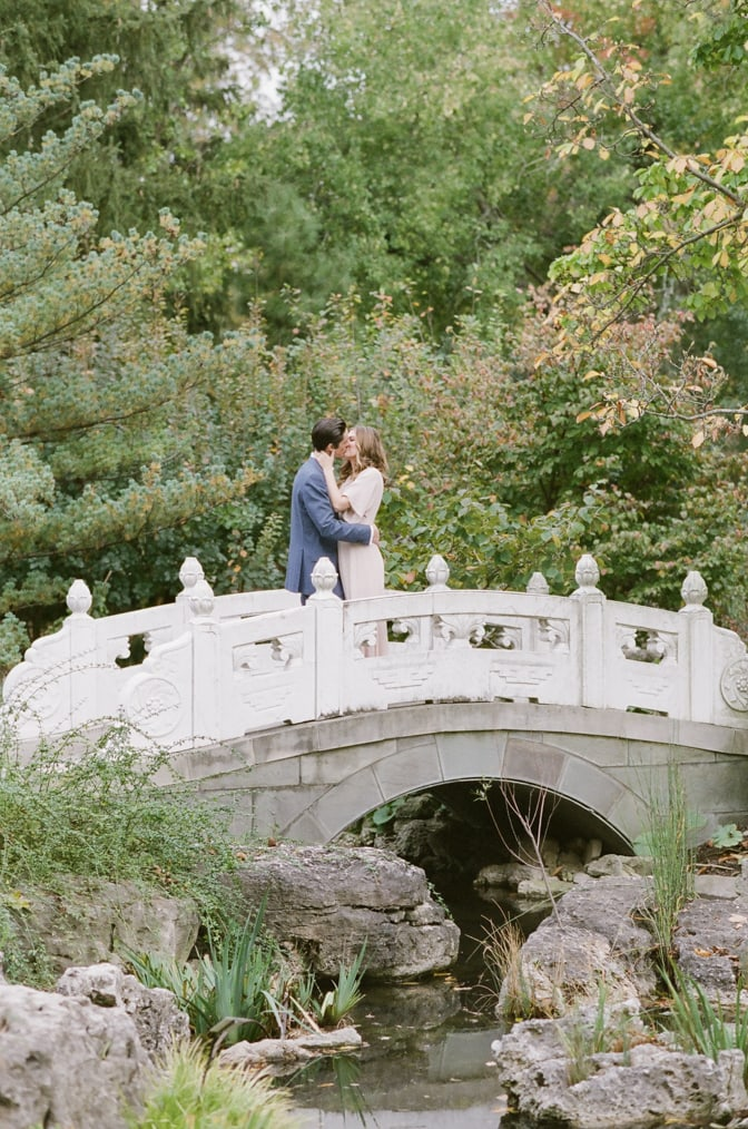 Bride and groom kissing each other on bridge at Chinese garden at Missouri Botanic Garden