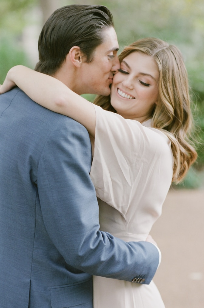 Groom kissing his bride on her cheek while embracing each other