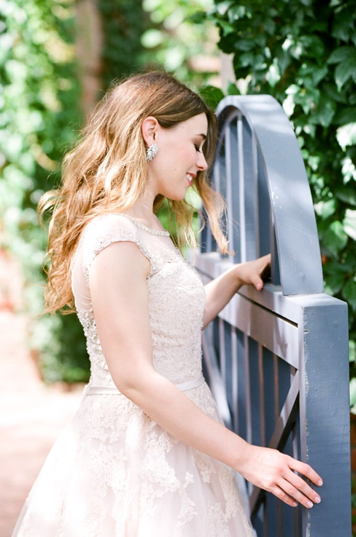 Bride standing next to a blue gate at The English Walled Gardens in Chicago
