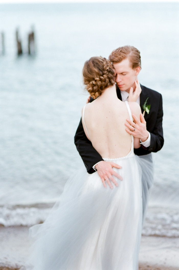 Bride and groom embracing each other during their wedding session at North Avenue Beach in Chicago