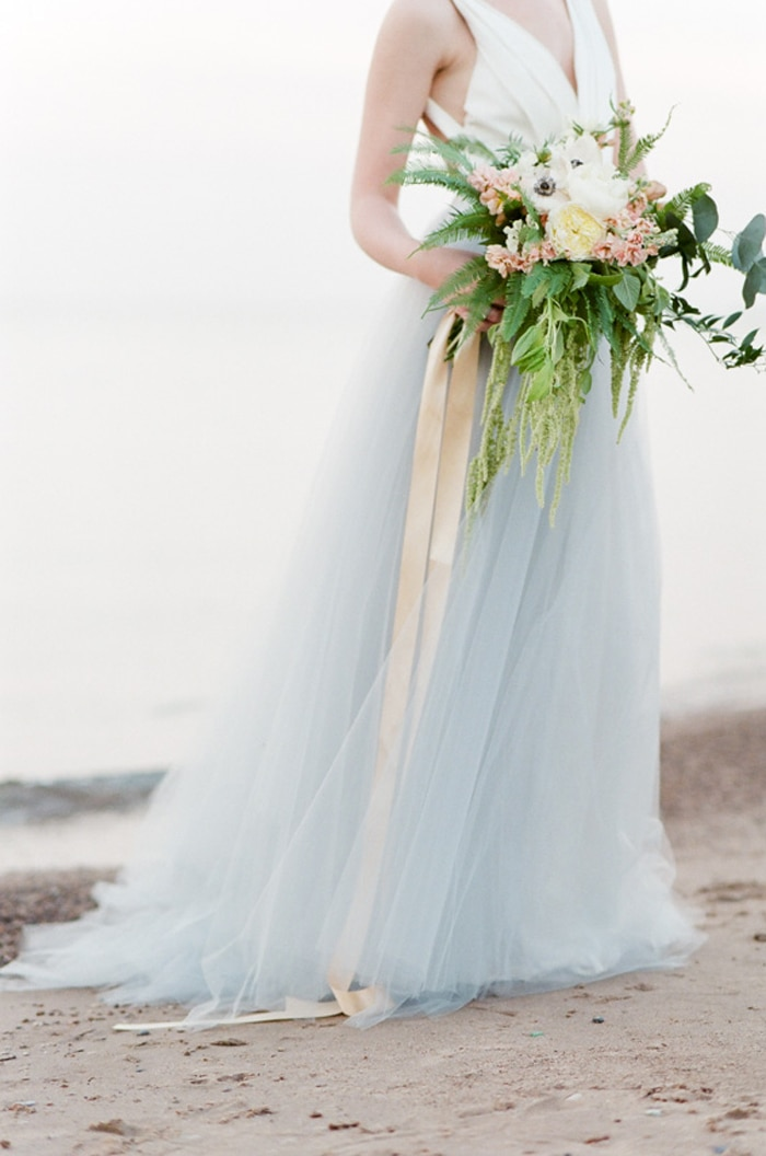 Woman in blue tulle dress holding a floral green bouquet