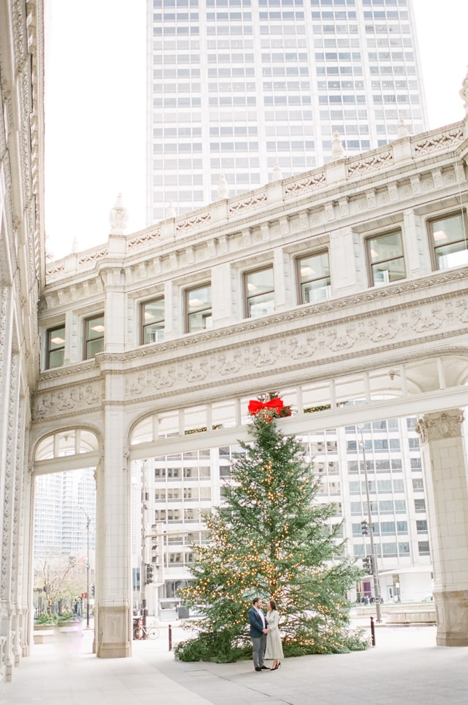 Bride and groom standing in front of the Christmas tree set up at Wrigley Building in Chicago