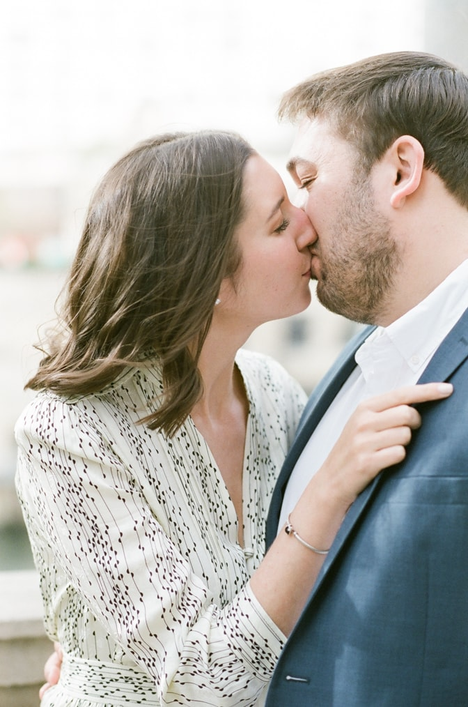 Bride to be kissing her groom to be during Chicago engagement