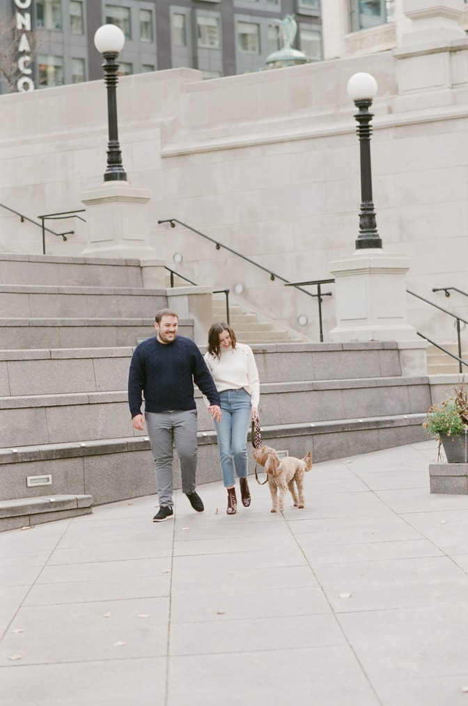 Engaged couple walking their dog along Chicago Riverwalk during their winter engagement session