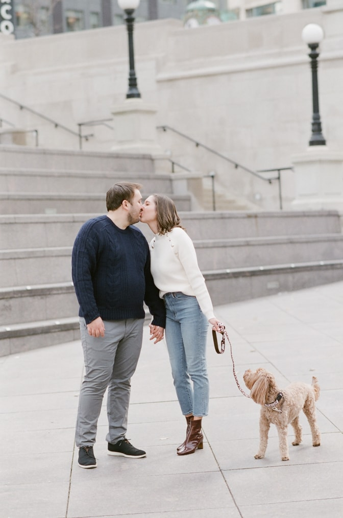 Engaged couple kissing each other in front of their during their Chicago engagement