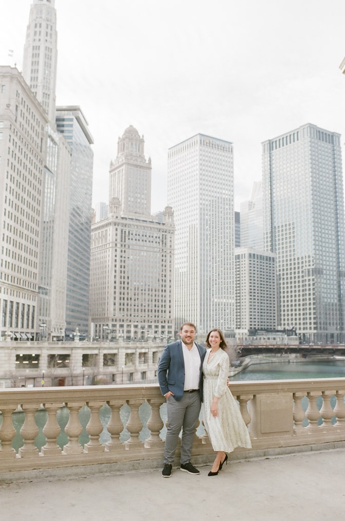 Engaged couple standing next to Wrigley Building during their Chicago engagement session