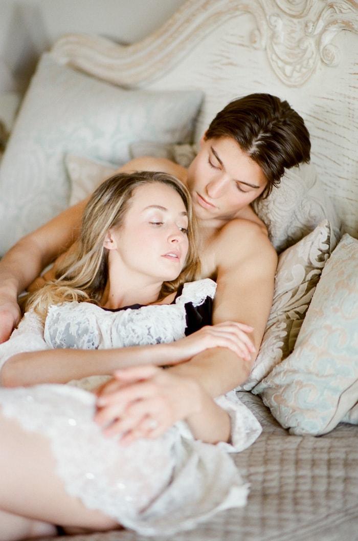 Groom embracing his bride in bed