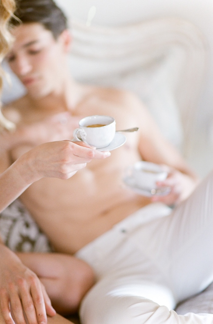 Closeup of engaged couple holding glass coffee cups