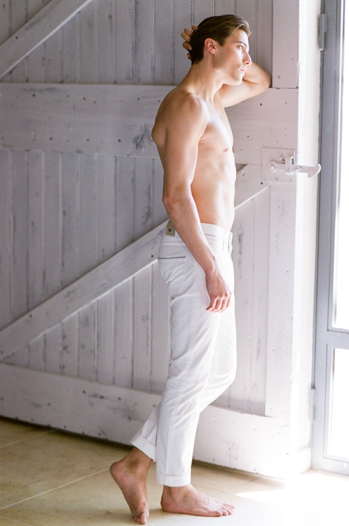 Groom in his white trousers leaning on a window during his boudoir session