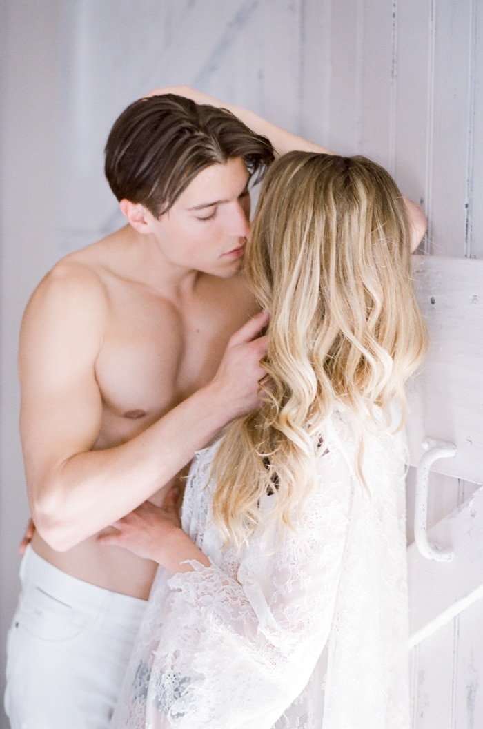 Groom kissing his bride while leaning on a white window shade