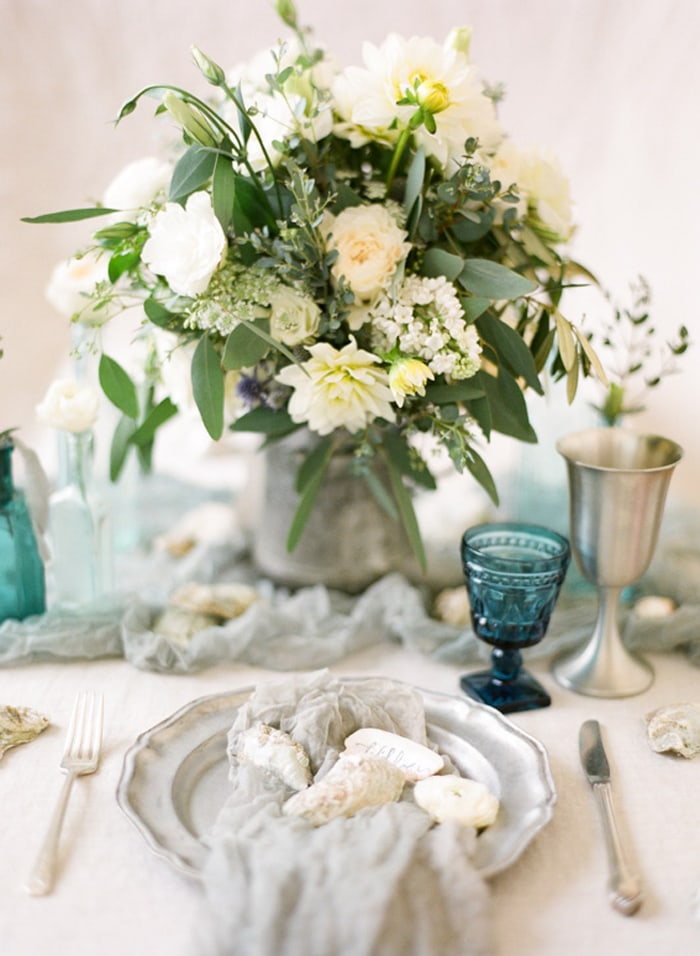 Floral wedding centerpiece with white and green blooms located on a grey silk linen from Silk and Willow