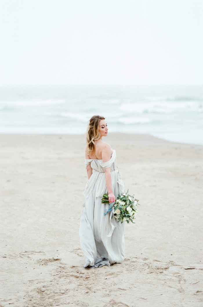 Chicago Bride holding her wedding bouquet and looking into the lake at North Avenue Beach