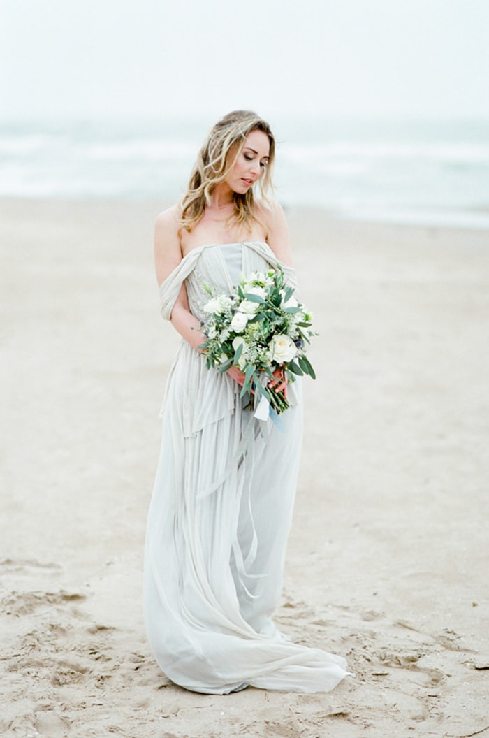 Bride standing at the Chicago beach and holding her wedding bouquet