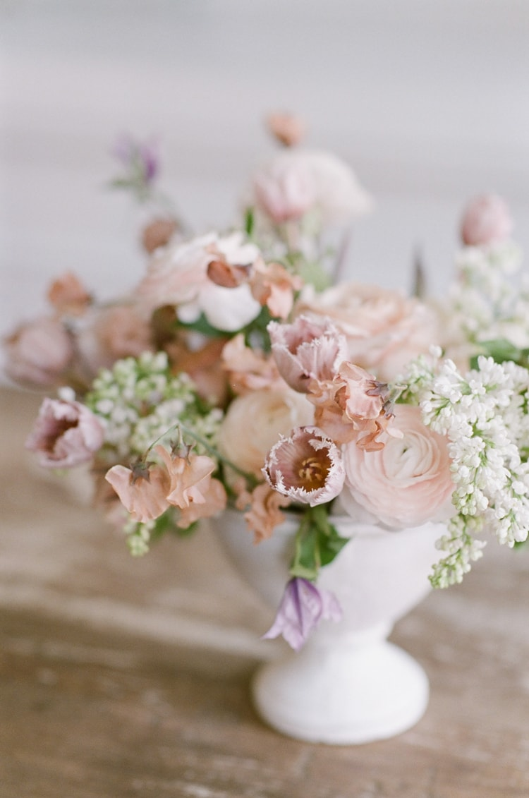 Wedding reception floral centerpiece containing blush and white florals