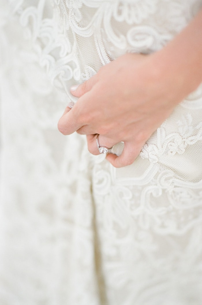 Closeup of 2-carat engagement ring on Claire Pettibone lace dress