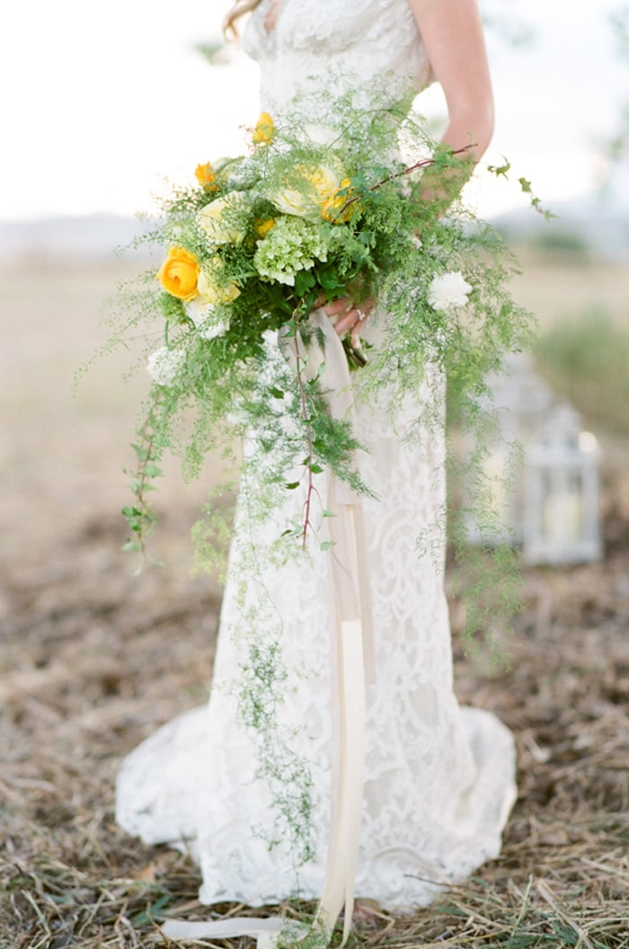 Closeup of wedding bouquet with yellow and white blooms surrounded by greenery