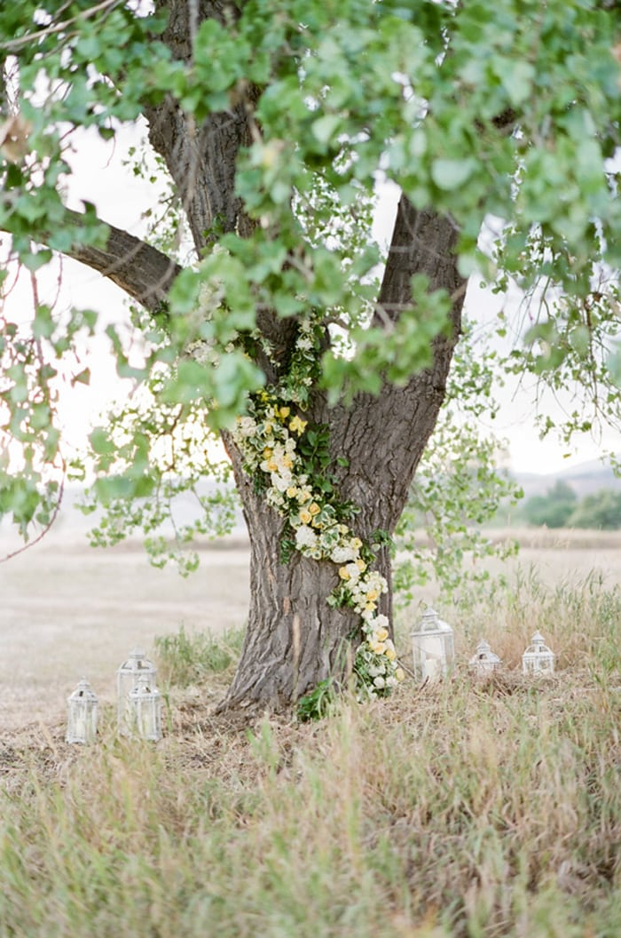 Wedding ceremony site of a tree adorned with yellow, white and green flowers