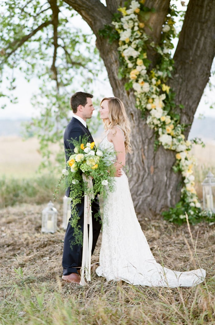 Bride and groom tying their knot under a tree at their Colorado wedding
