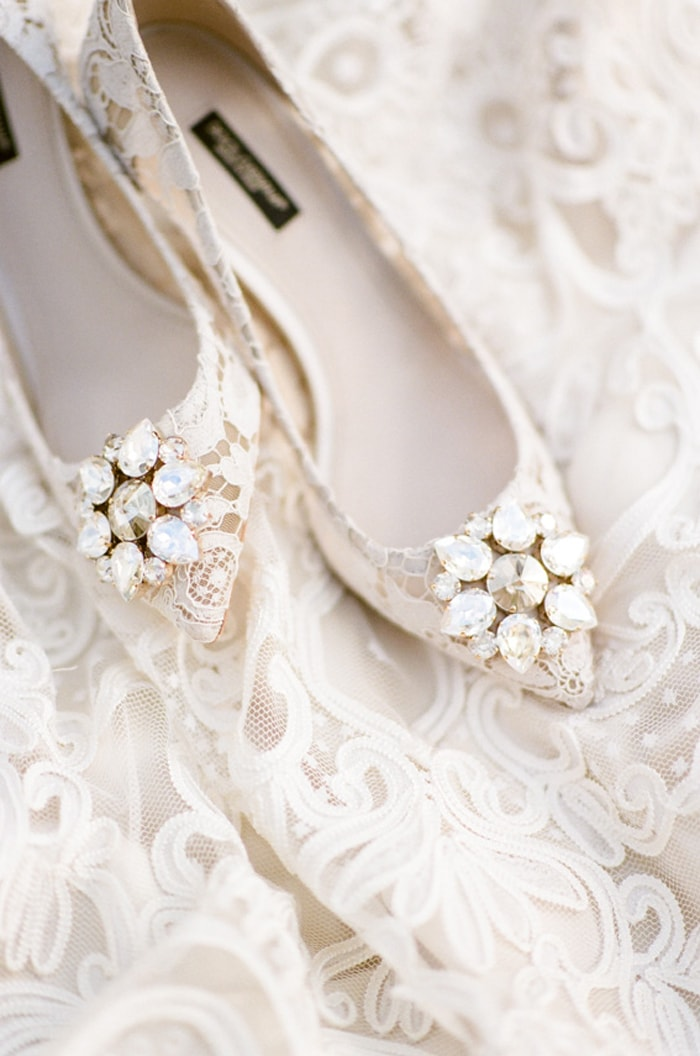 Closeup of Dolce Gabbana lace flat shoes with diamond brooch