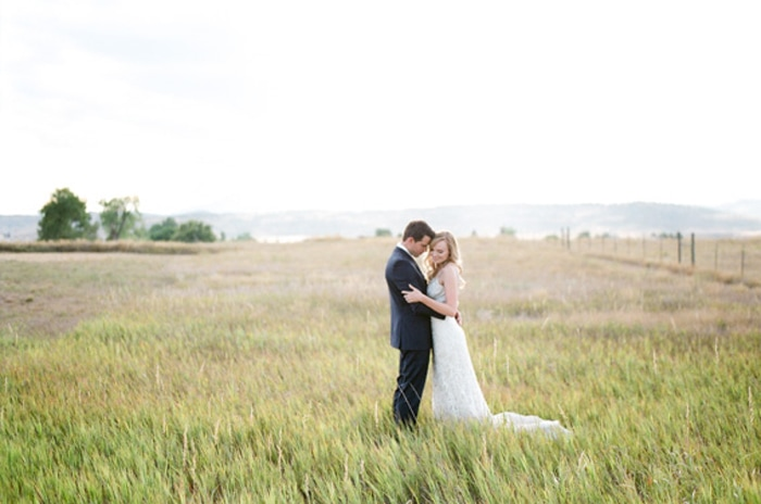 Bride and groom embracing each other in a wild grass field on their Colorado wedding day