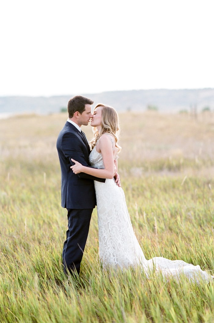 Bride and groom kissing each other in a wild grass field in Colorado