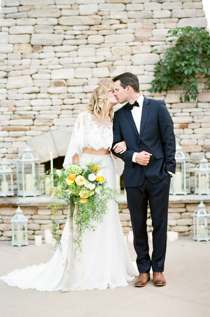Bride and groom kissing each other in front of a grey fireplace