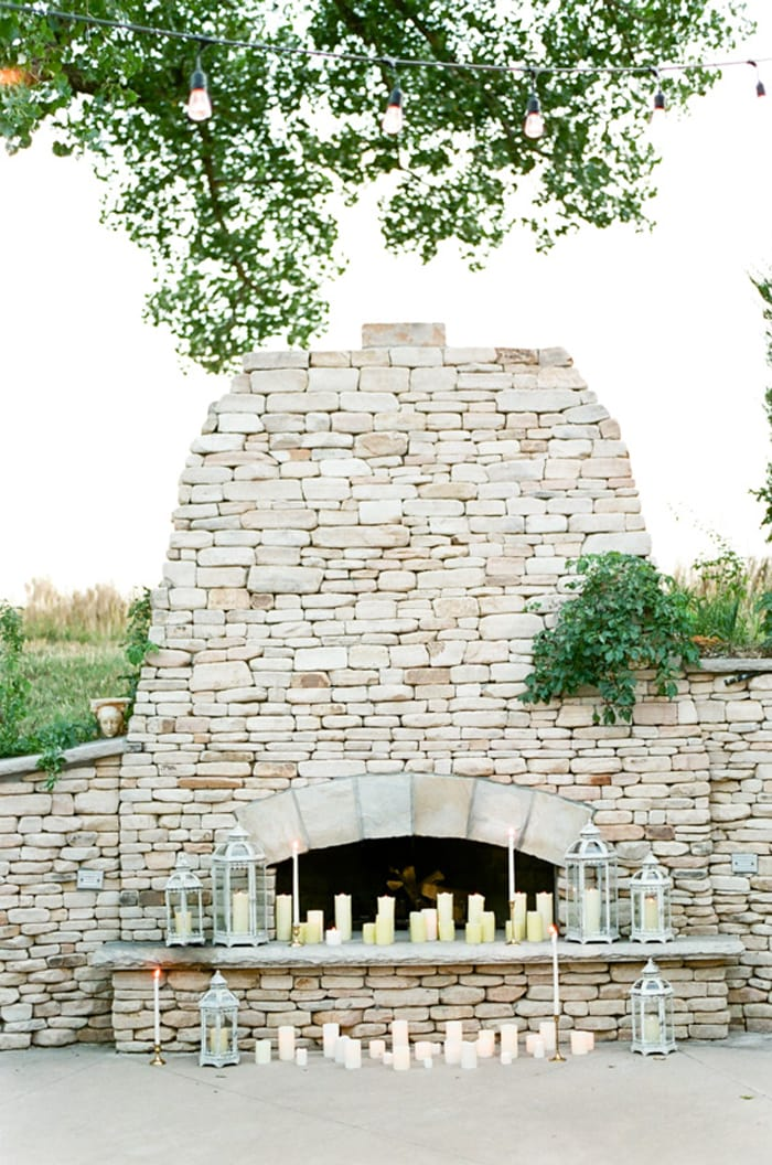 Grey stone fireplace adorned with candles