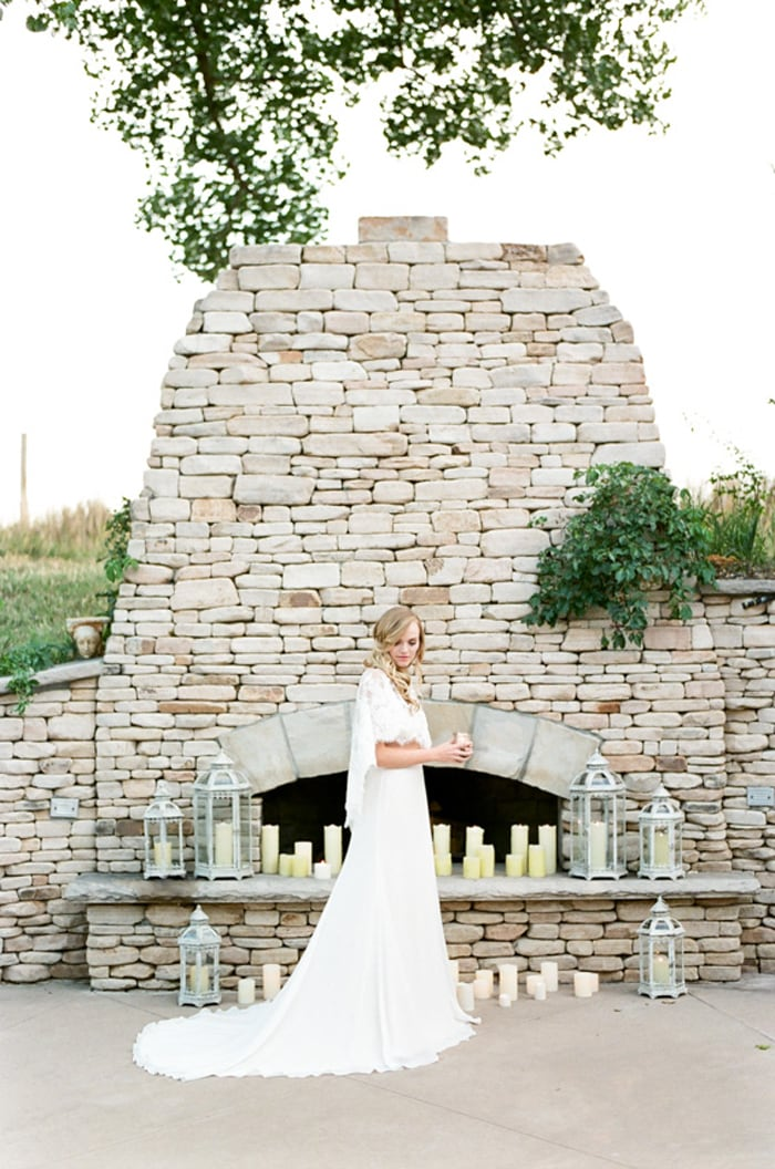 Bride in her lace wedding gown in front of an outdoor fireplace