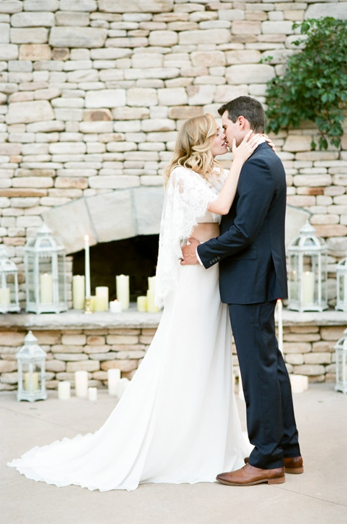 Bride and groom kissing each other in front of an outdoor fireplace
