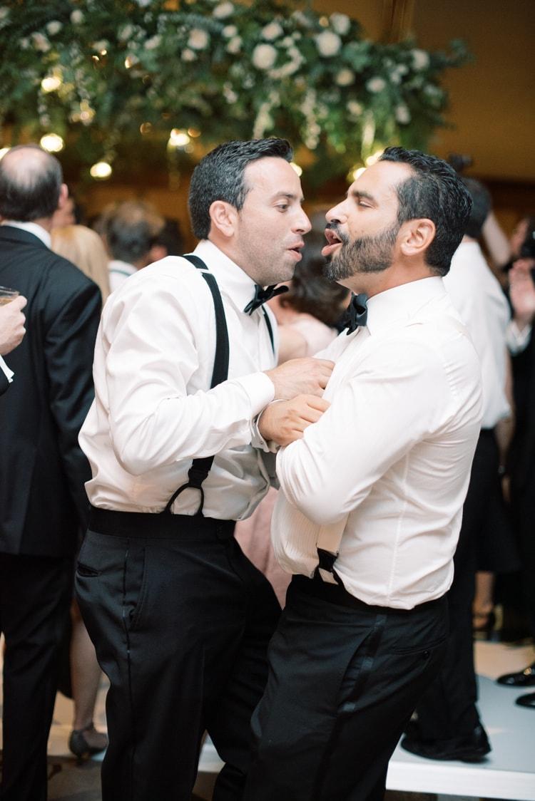 Groomsmen dancing together at wedding reception