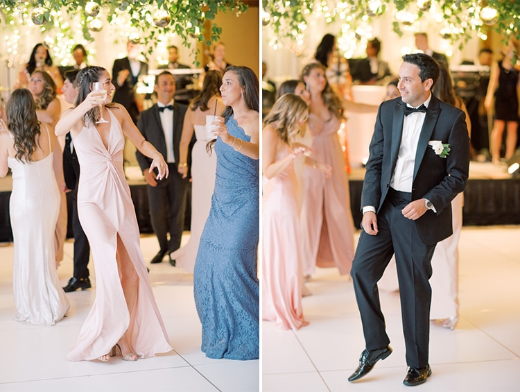 Wedding guests dancing on dance floor under a floral ceiling installation