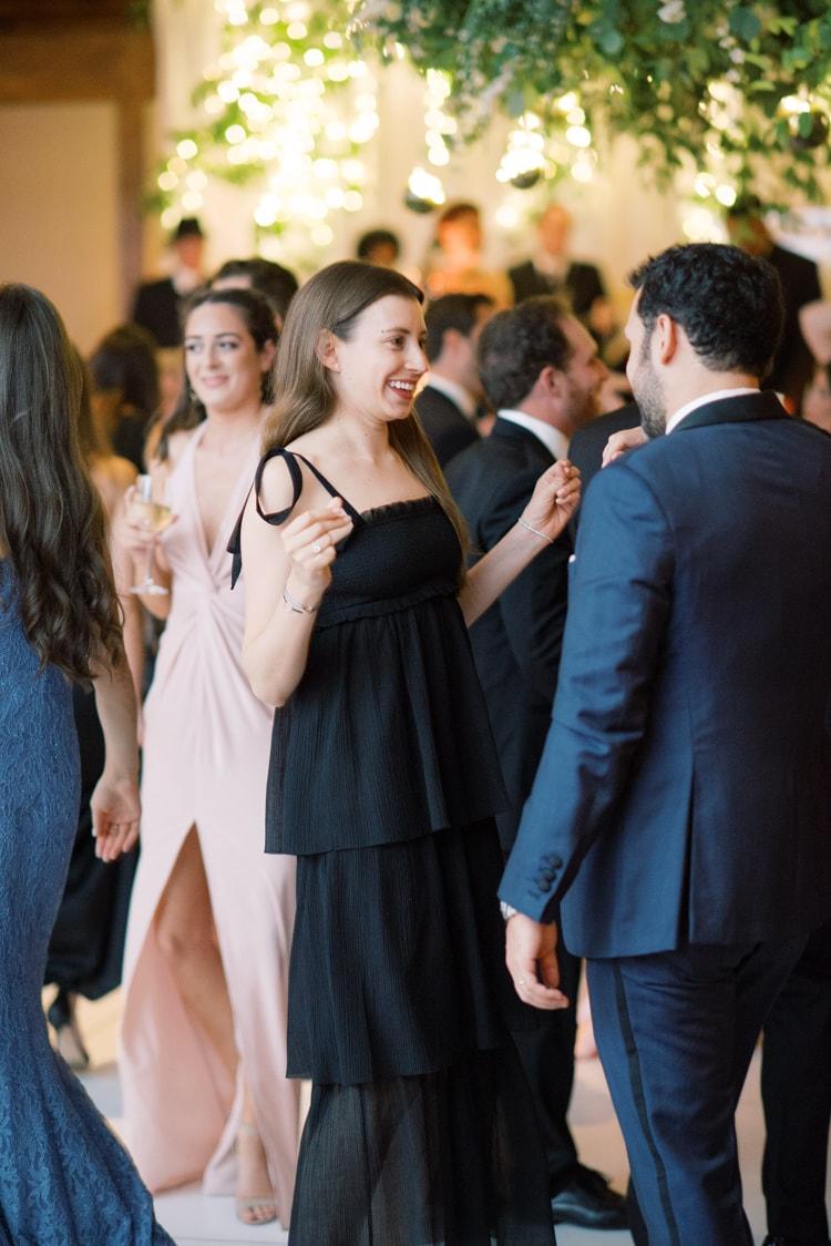 Woman in black dress dancing at wedding reception
