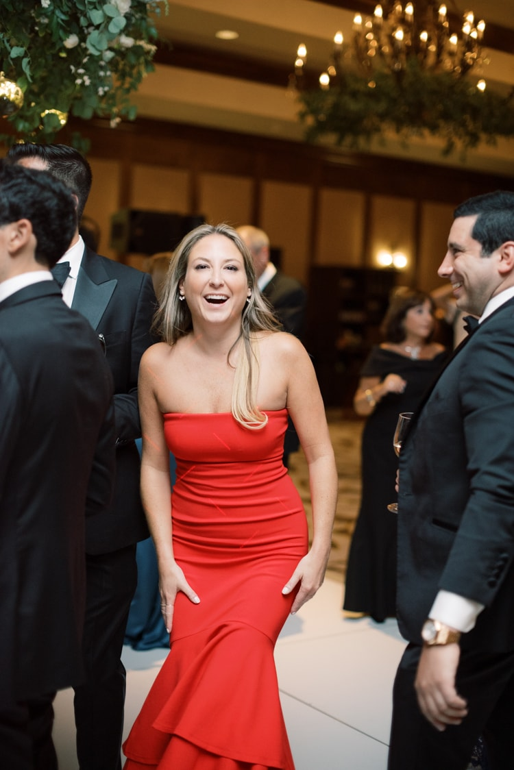Woman in red dress dancing during wedding reception and smiling into the camera
