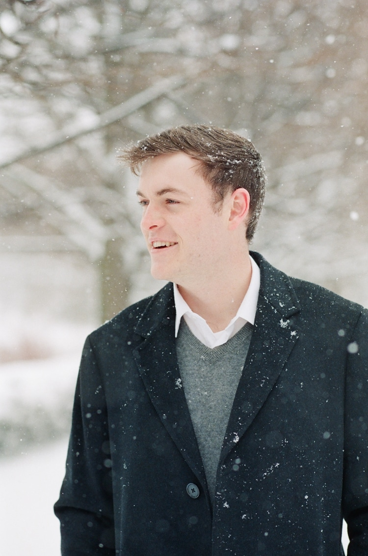 Groom to be dressed in his black coat at the Chicago Botanic Garden