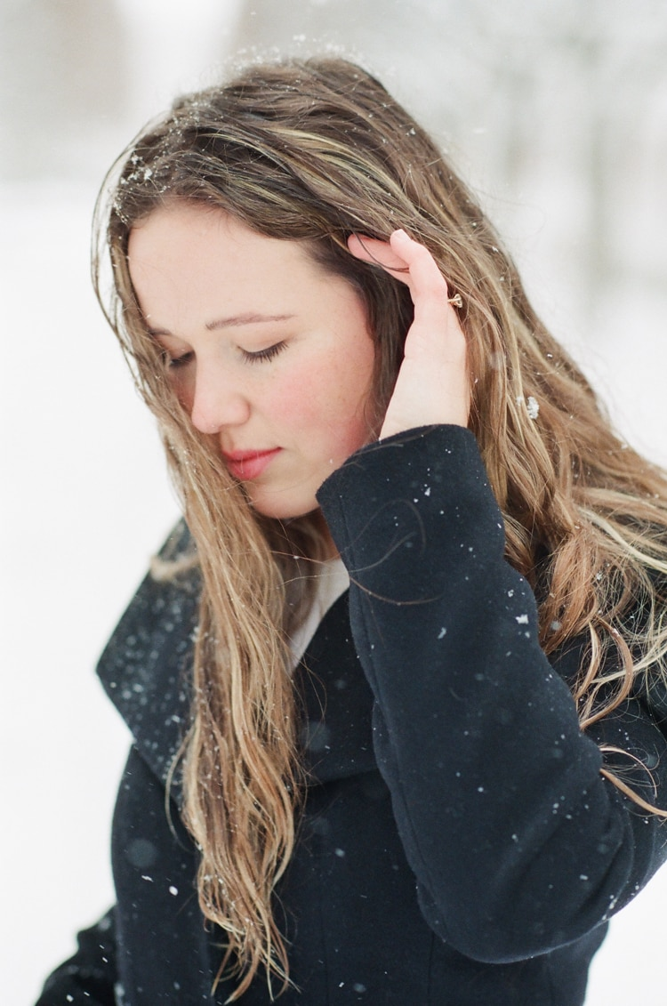 Bride holding her hair while standing in snow