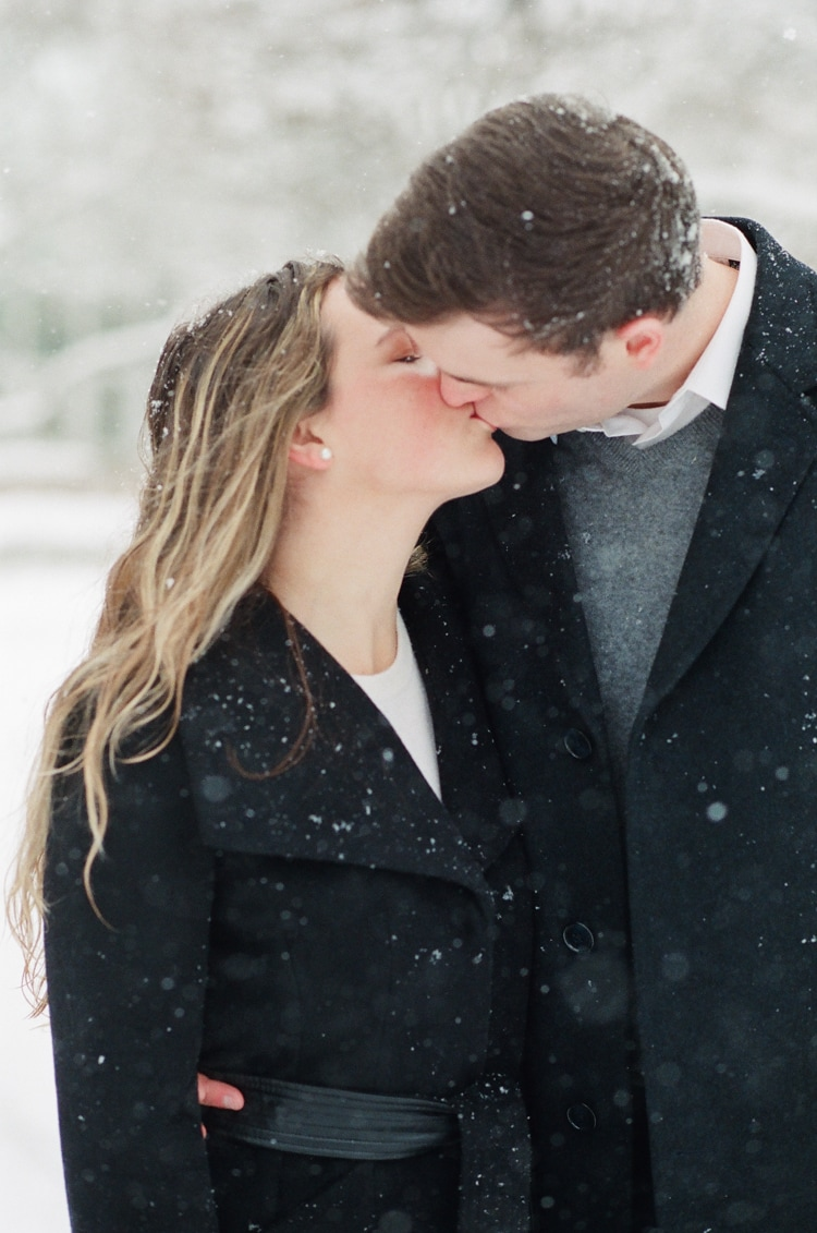 Closeup of an engaged couple kissing each other during their snow engagement session