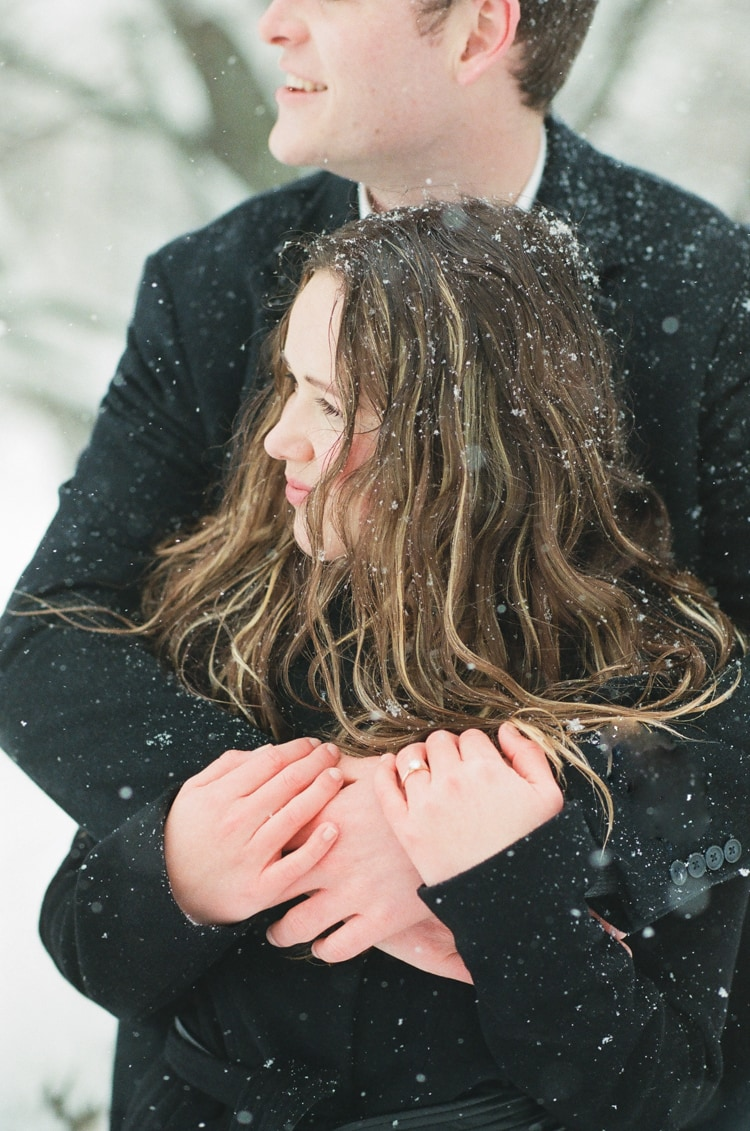 Engaged couple embracing each other while it's snowing