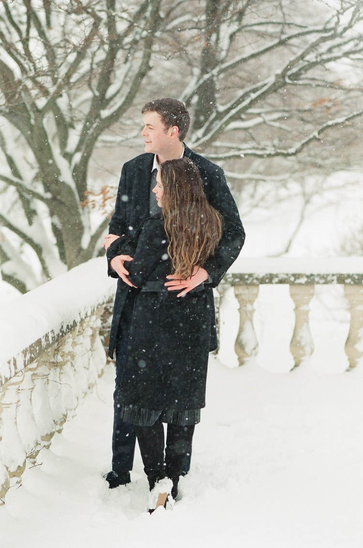 Engaged couple standing at the Chicago Botanic Garden in snow