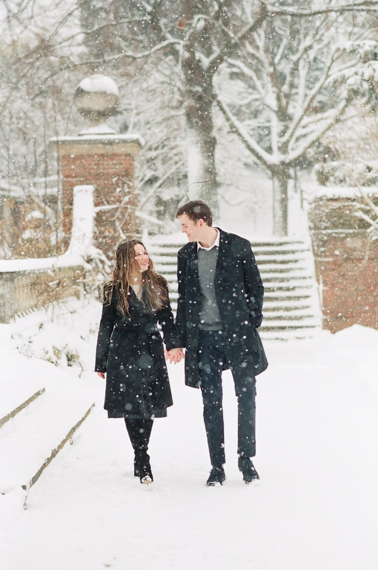 Engaged couple walking at the English Walled Garden covered in snow